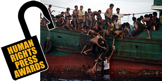 Rohingya migrants pass food supplies dropped by a Thai army helicopter to others aboard a boat drifting in Thai waters off the southern island of Koh Lipe in the Andaman sea on May 14, 2015.  A boat crammed with scores of Rohingya migrants, including many young children, was found drifting in Thai waters on May 14, with passengers saying several people had died over the last few days.  AFP PHOTO / Christophe ARCHAMBAULT