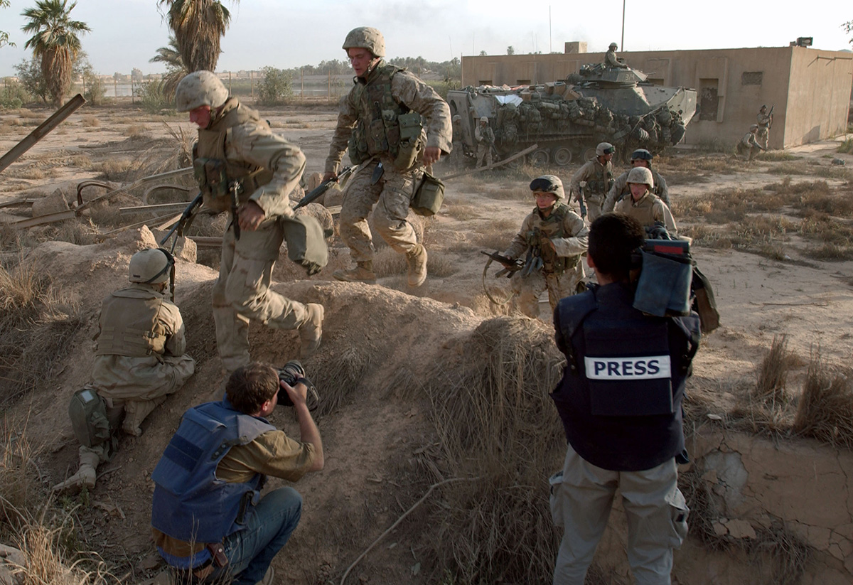 US Marines rush through a trench after they were attacked by Iraqis from the presidential palace area 11 April, 2003 in Baghdad as photographers work from the trench. US forces were battling pockets of resistance two days after the collapse of Iraqi president Saddam Hussein's regime.  AFP PHOTO/ERIC FEFERBERG / AFP PHOTO / ERIC FEFERBERG