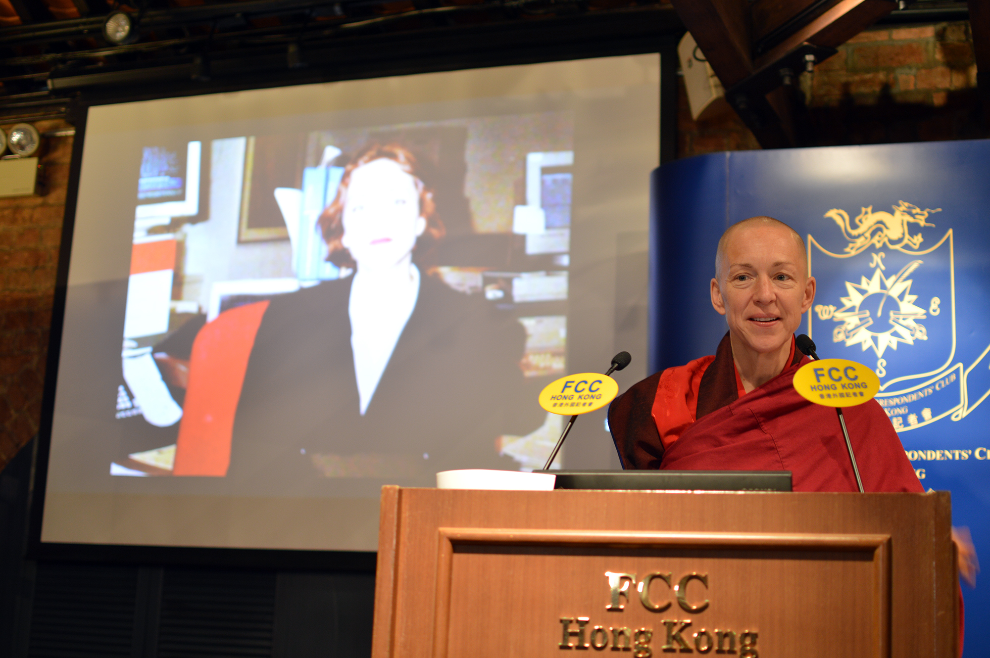 Emma Slade, standing in front of a photo from her days as a high-flying banker, told FCC members about her journey to becoming a Buddhist nun. Photo: Sarah Graham/FCC