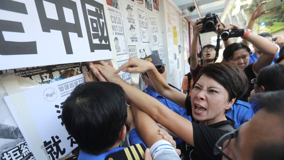 Students clash in front of a wall of posters for and against independence for Hong Kong. Photo: SCMP