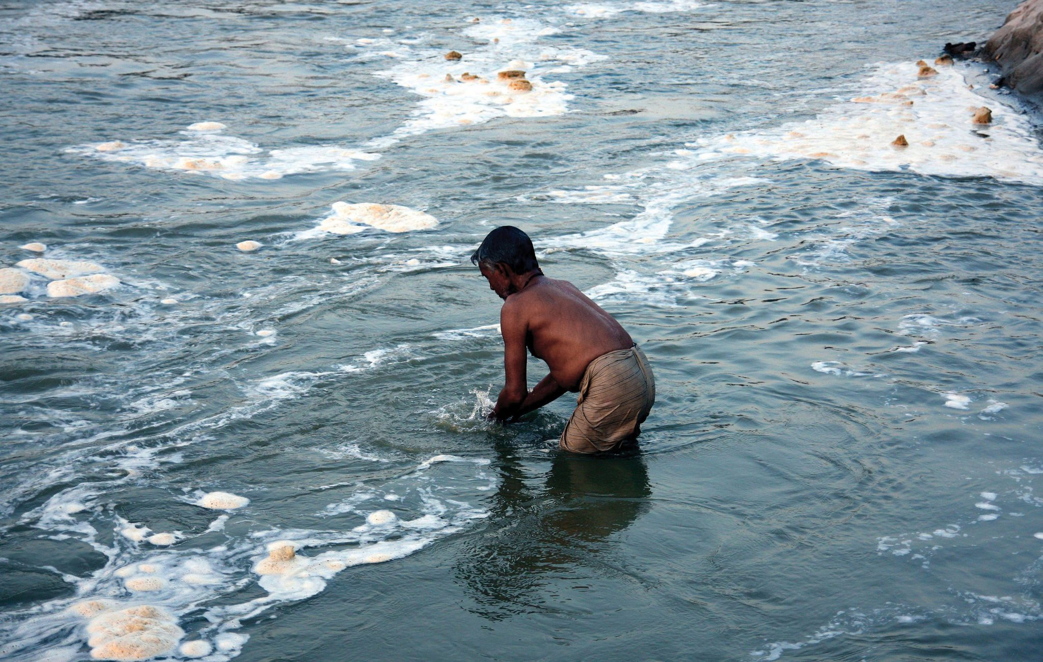 A Hindu devotee takes a holy dip in the polluted river Ganga (Ganges) in Allahabad.