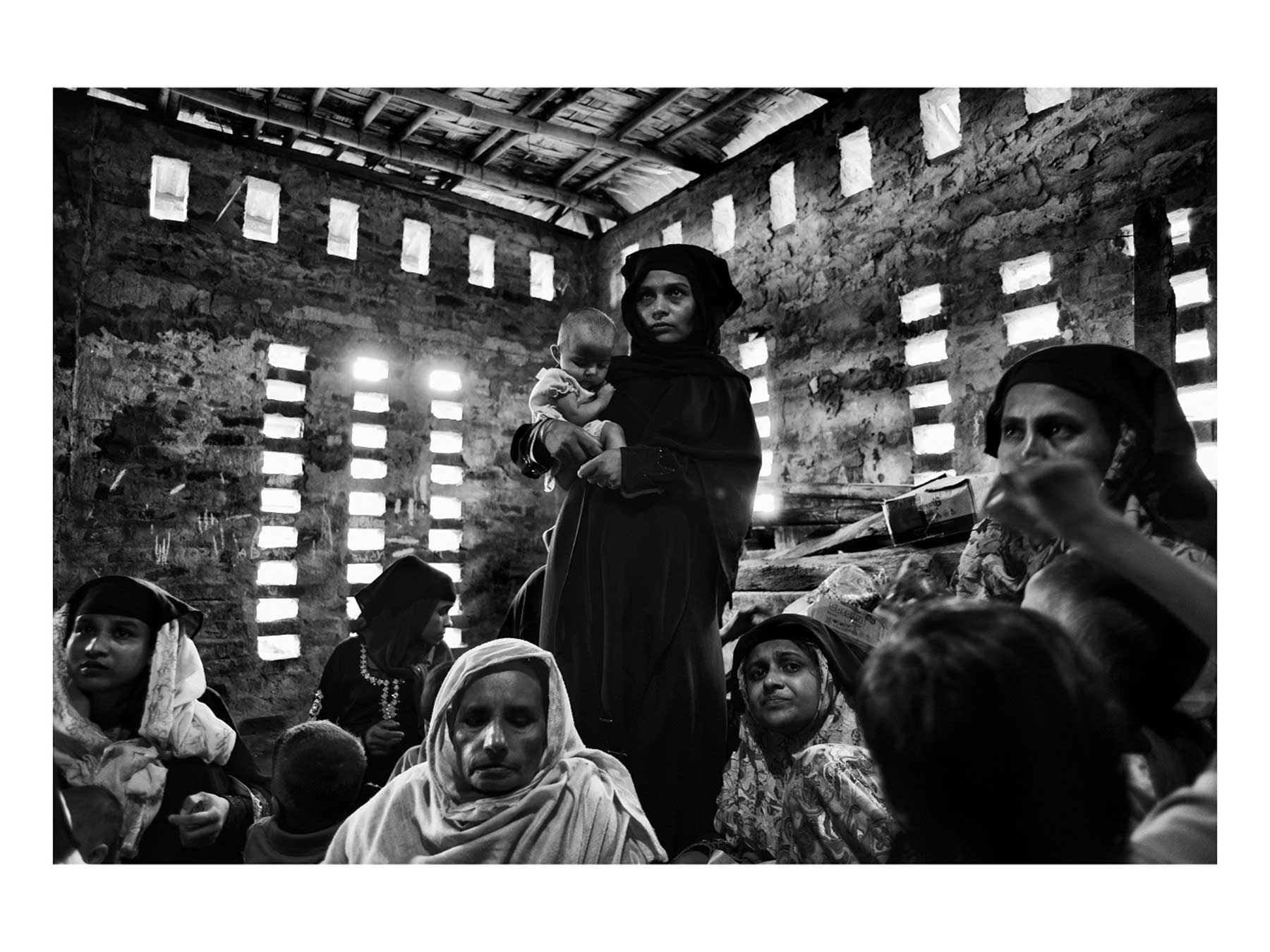 A Rohingya mother and child wait with other Rohingya to receive assistance at a makeshift medical clinic near the Kutupalong refugee camp. Photo by Greg Constantine.
