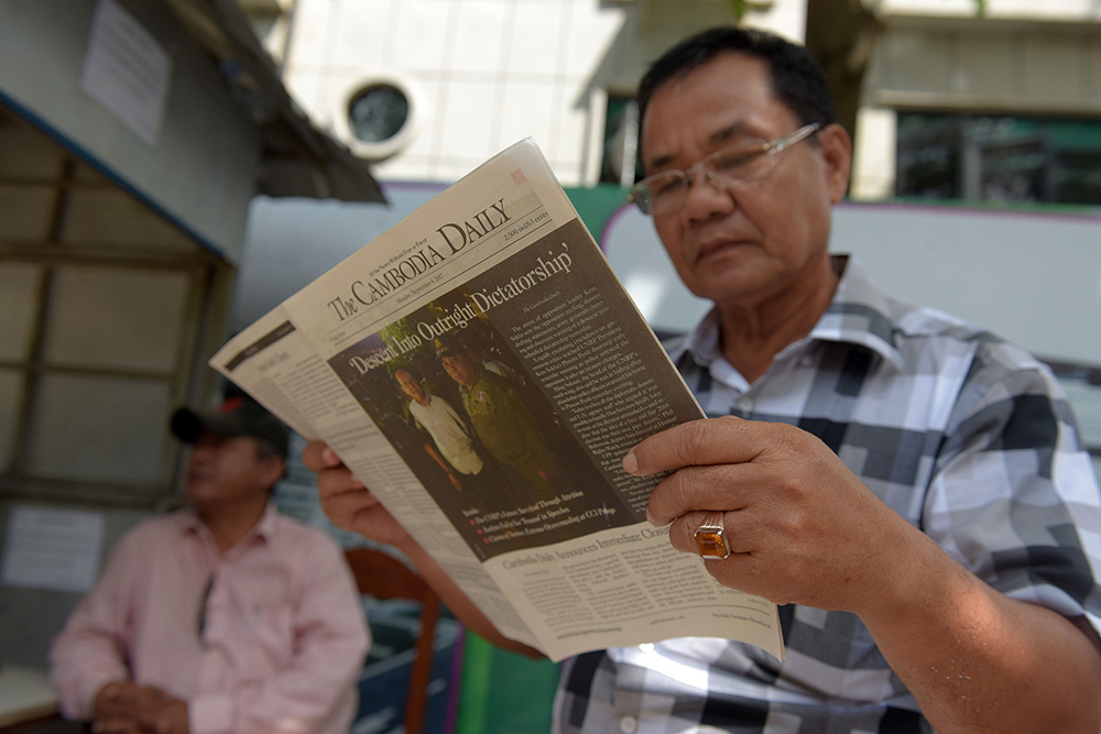 A Cambodian man reads the last edition of The Cambodia Daily in Phnom Penh