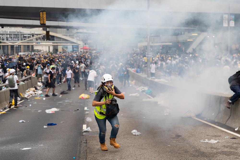 Hong Kong June 12, 2019: A reporter running for cover as tear gas canisters explode during clashes with Anti Extradition Bill protesters outside the Central Government Office in Hong Kong.