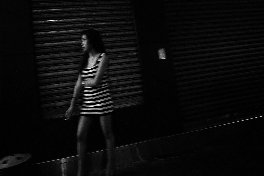 Woman Smoking on a Street Corner, Wan Chai, Hong Kong, 2016. Photo: Rob Gerhardt
