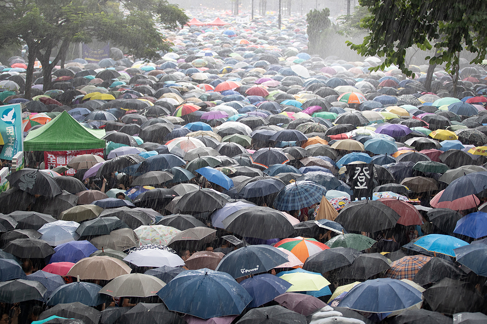 Demonstrators overflow Victoria Park under the heavy rain. Photo: May James