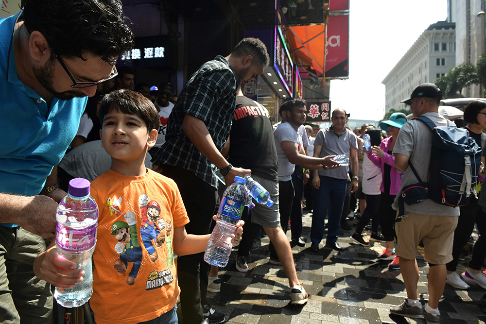 Members of the South Asian community hand out bottles of water to people taking part in a pro-democracy march outside Chungking Mansions