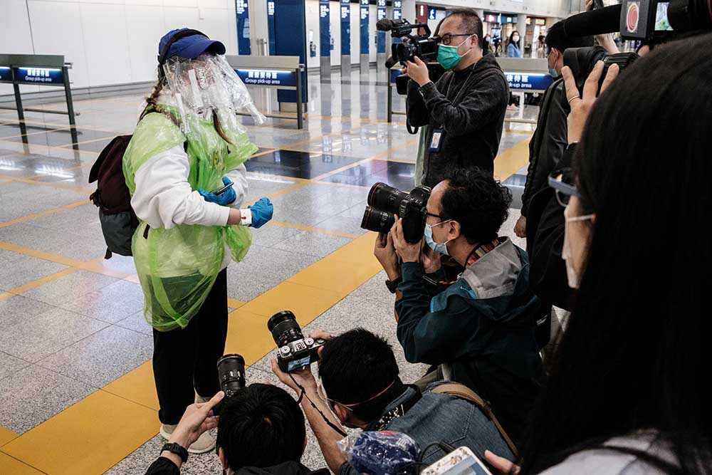 A passenger is surrounded by the media while showing off her quarantine tracking wrist band at Hong Kong's international airport