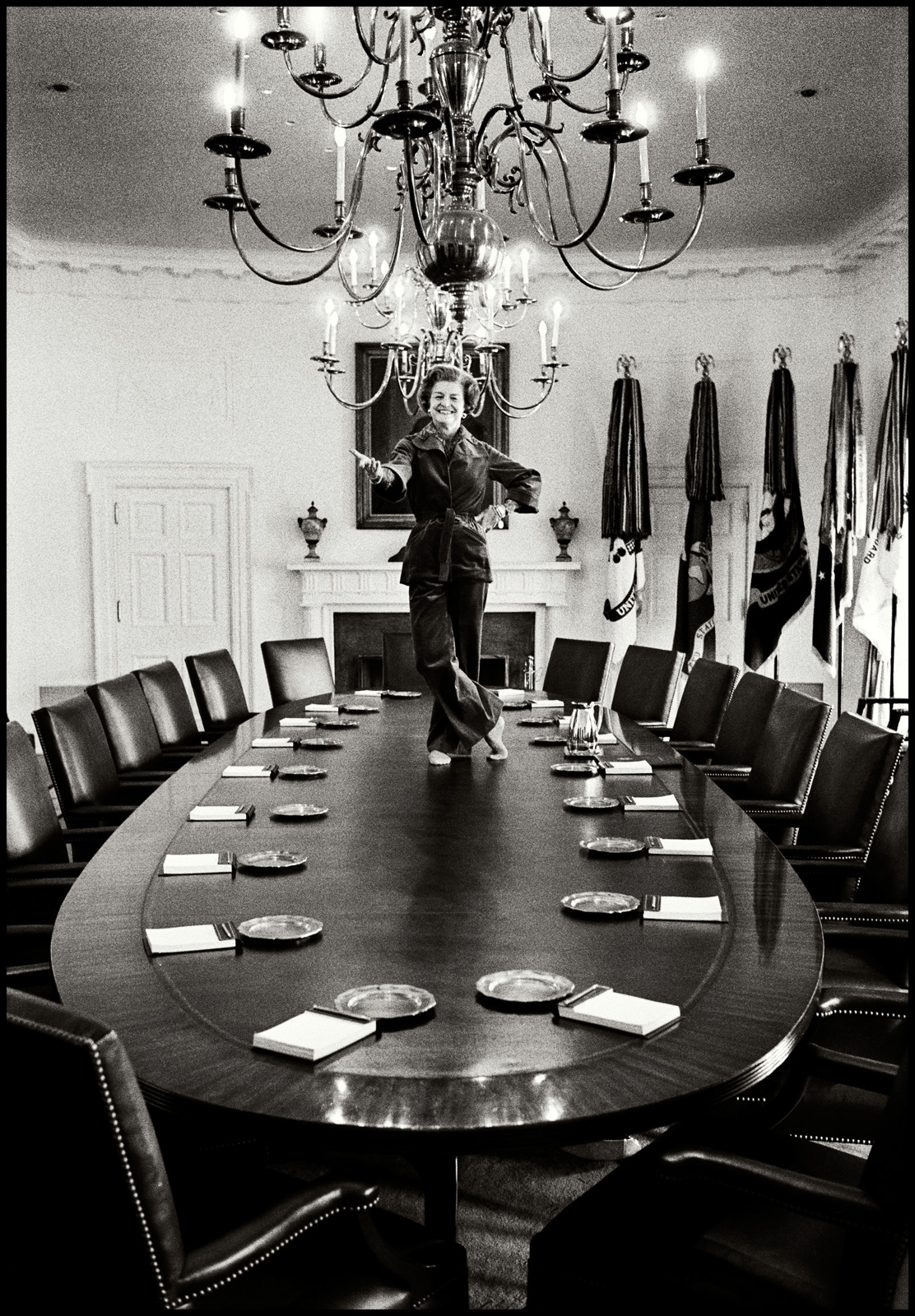 First Lady Betty Ford strikes a playful pose on the Cabinet Room table, January 19, 1977, the day before leaving the White House in Washington D.C. (Photo by David Hume Kennerly)