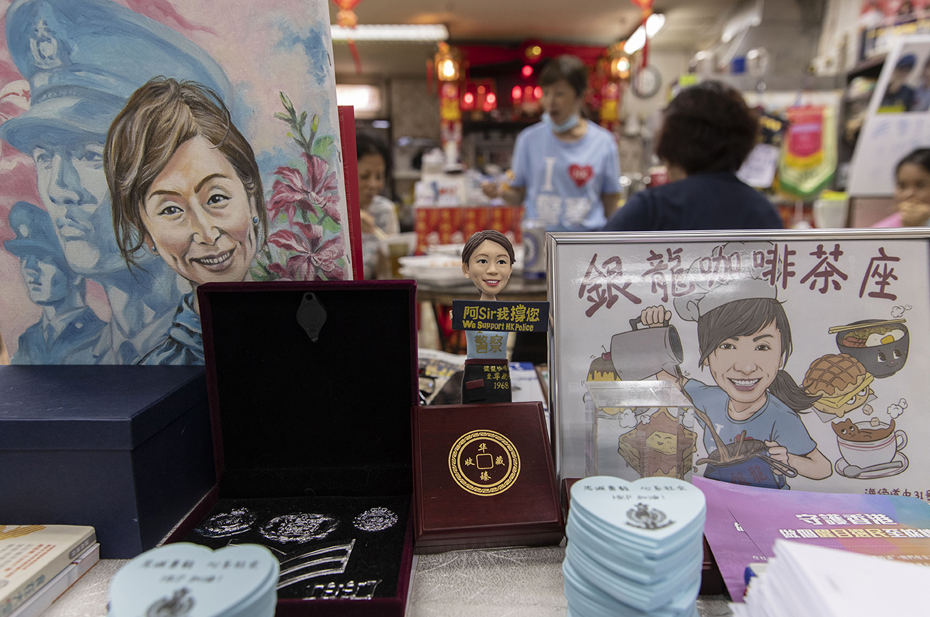 Café owner in blue T-shirt with 'blue' souvenirs for sale