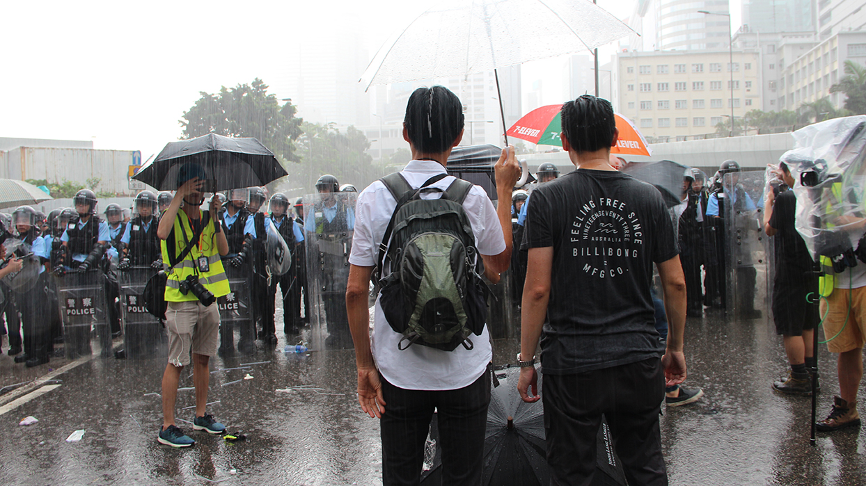 Lawmakers Eddie Chu and Jeremy Tam face riot police on July 1, 2019