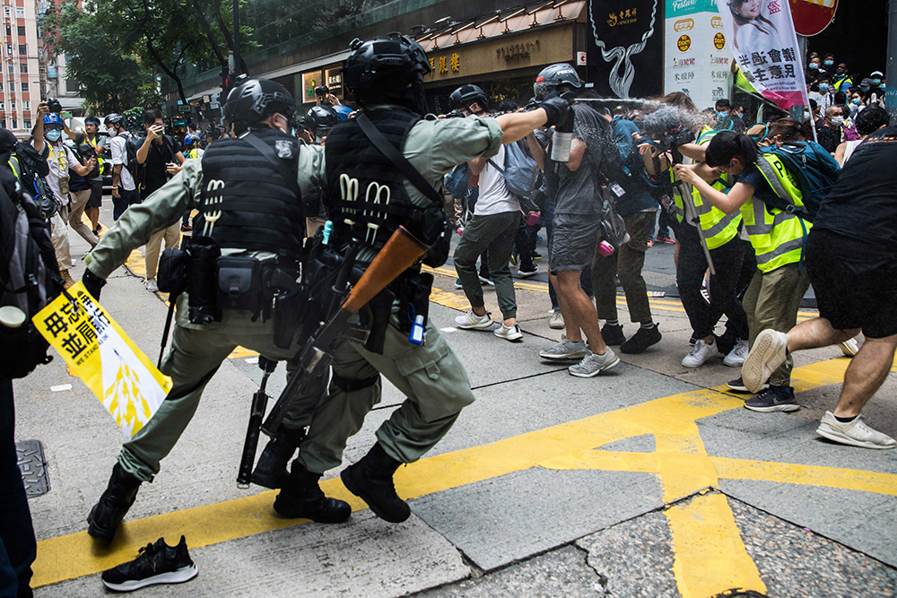 Riot police pepper spray a group of journalists on 1 July, 2020. PHOTO: DALE DE LA REY / AFP