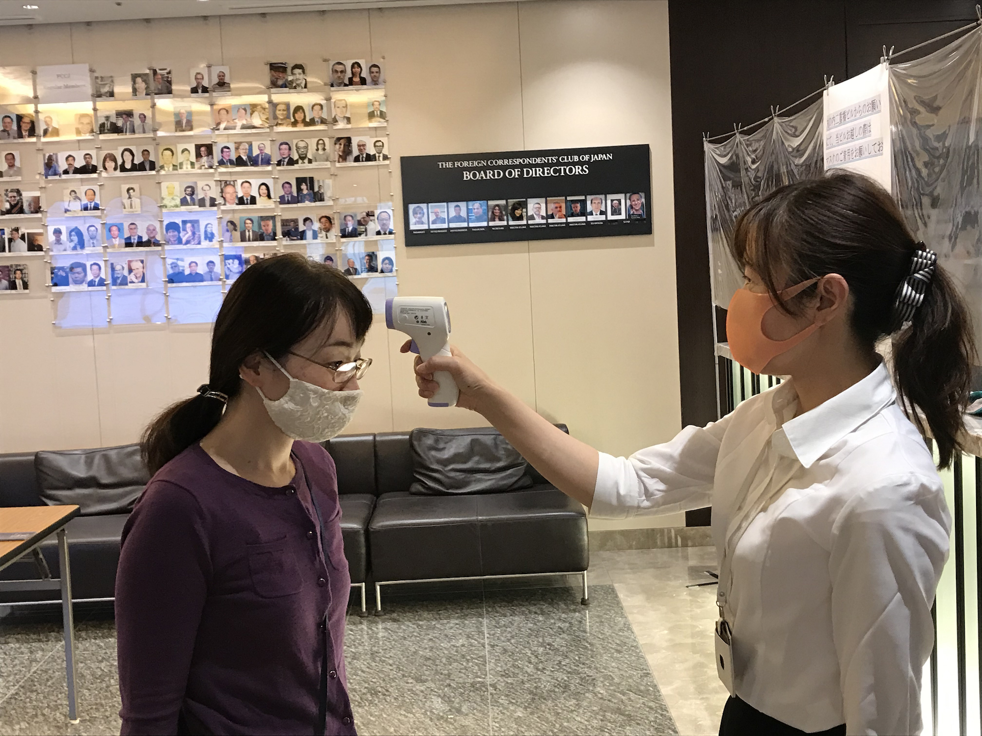 A member gets her temperature checked at the FCCJ in Tokyo.